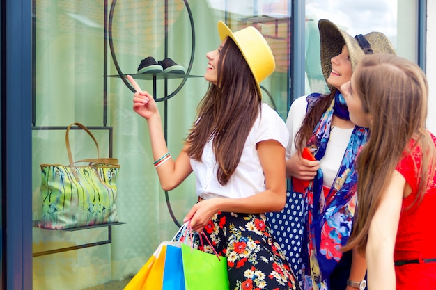 Surprised bright women females girls friends in colorful dresses and hats in shopping mall looking for new fashion clothes in shop's window. Premium Photo