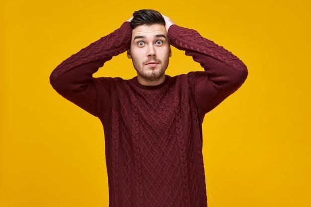 Удивленный самец с жучковыми глазами в теплом свитере, держась за голову руками, Бесплатные Фотографии