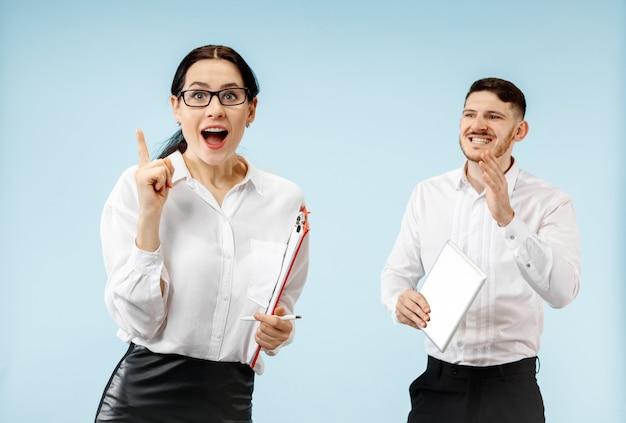 L'uomo d'affari sorpreso e la donna sorridente su uno sfondo blu studio Foto Gratuite