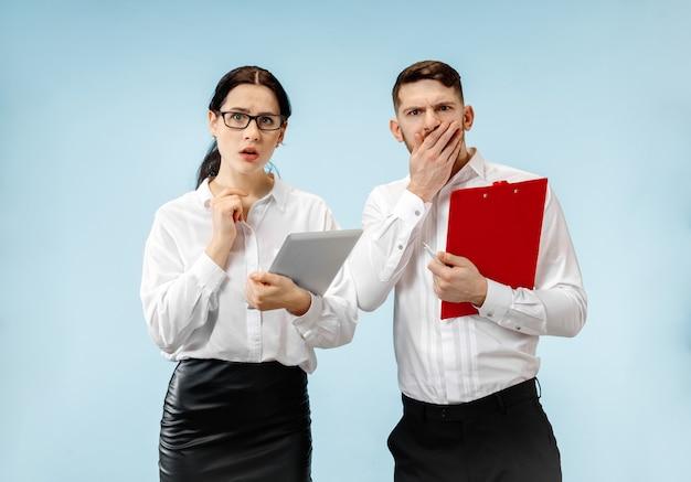 L'uomo d'affari sorpreso e la donna sorridente su una parete blu Foto Gratuite