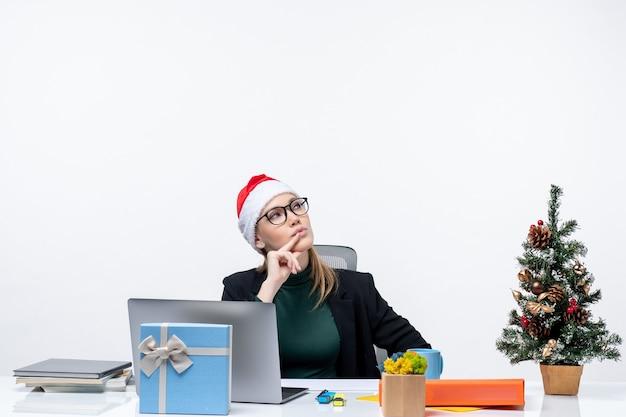 Donna d'affari sorpresa con cappello di babbo natale seduto a un tavolo con un albero di natale e un regalo su di esso e rivolto in alto sul lato sinistro su sfondo bianco Foto Gratuite