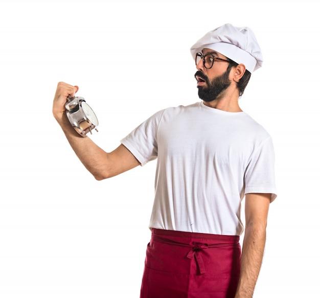 Sorpreso chef in possesso di un orologio su sfondo bianco Foto Gratuite