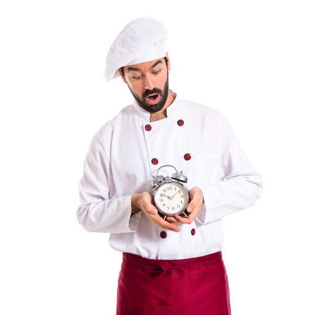Chef sorpreso che tiene un orologio su sfondo bianco Foto Gratuite