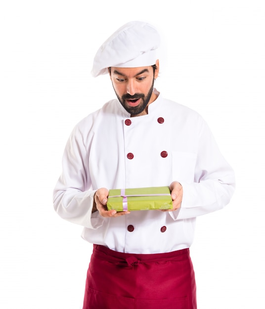 Surprised chef holding a present Free Photo