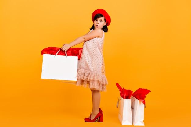 Удивленный ребенок позирует в туфлях матери. пораженная девочка десятилетнего возраста, держащая хозяйственную сумку на желтой стене. Бесплатные Фотографии