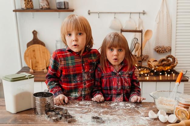 Bambini sorpresi che producono insieme i biscotti di natale Foto Gratuite