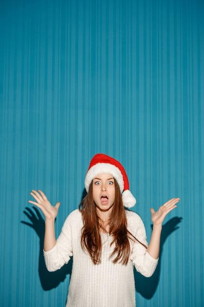 La ragazza sorpresa di natale che porta un cappello della santa sui precedenti blu Foto Gratuite