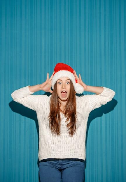 Sorpreso natale ragazza che indossa un cappello da babbo natale sullo sfondo blu studio Foto Gratuite
