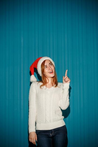 Sorpreso natale ragazza che indossa un cappello da babbo natale rivolto verso l'alto sullo sfondo blu studio rivolto verso l'alto Foto Gratuite