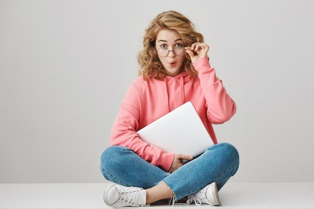 Удивленная кудрявая девушка с ноутбуком, выглядящая взволнованной Бесплатные Фотографии