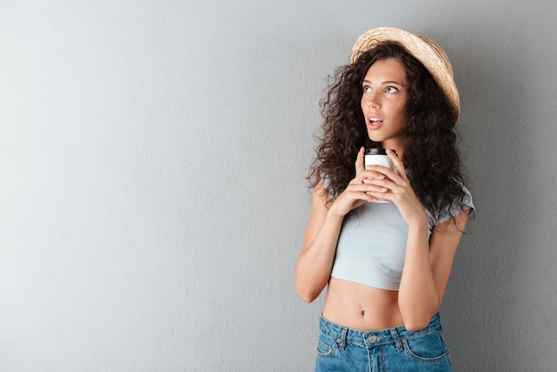 Surprised curly woman in hat drinking coffee and looking away Free Photo