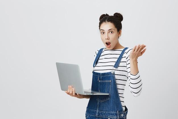 Ragazza carina sorpresa che sembra eccitata durante l'utilizzo del computer portatile Foto Gratuite