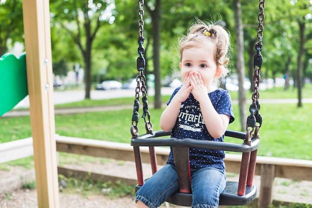 Surprised cute little girl sitting on swing Free Photo