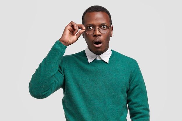 Surprised dark skinned male teacher keeps hand on rim of glasses, wears elegant white shirt and green sweater Free Photo