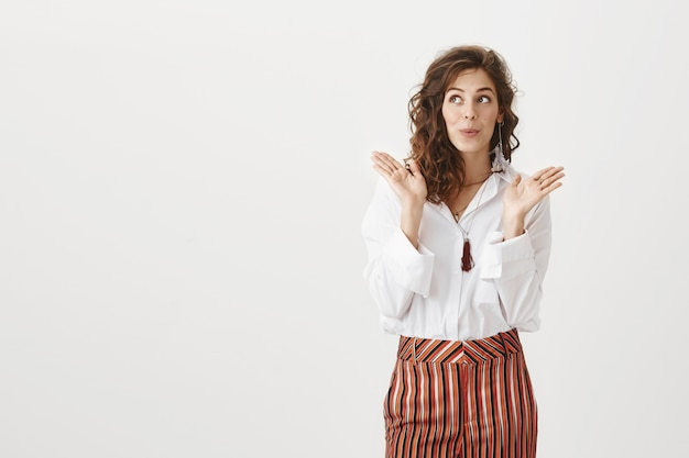 Surprised enthusiastic woman claps her hands and looks left impressed Free Photo