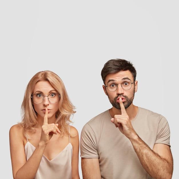 驚いたヨーロッパの女性と男性は沈黙のジェスチャーをし、機密情報を伝え、静かにするように頼む 無料写真