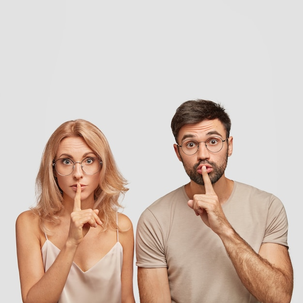 Surprised european woman and man makes silence gesture, tells confidential information, ask to be quiet Free Photo