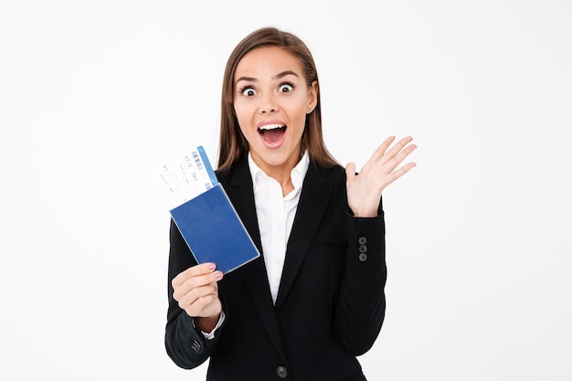 Surprised excited pretty businesswoman holding tickets and passport Free Photo