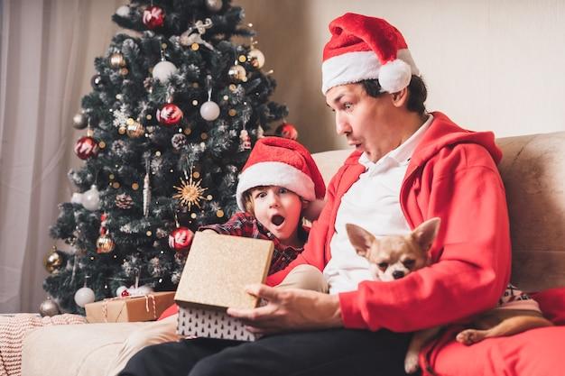 Удивленная семья в шляпе санта-клауса, отец и ребенок мальчик открывают рождественский подарок дома Premium Фотографии