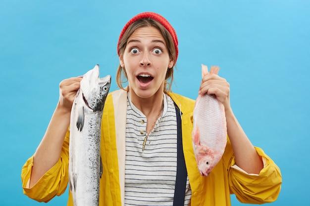 Pescatore femminile sorpreso tenendo il pesce Foto Gratuite
