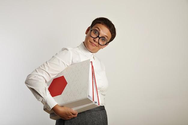Insegnante donna divertente sorpresa indagatrice e tiene due grandi cartelle di documenti con un nuovo piano educativo Foto Gratuite