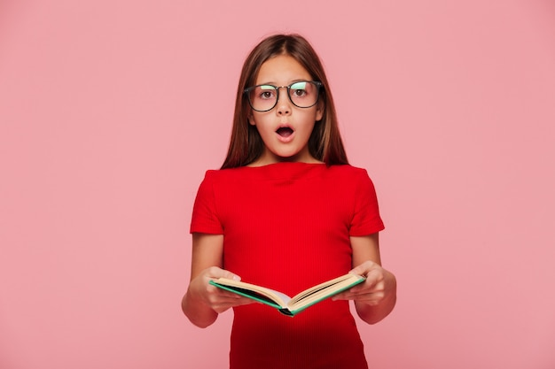 Surprised girl nerd looking while reading book Free Photo