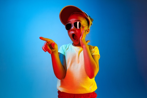 Surprised girl pointing isolated on blue wall Free Photo