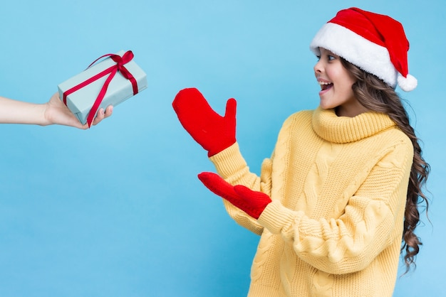 Surprised girl receiving gift on winter Free Photo