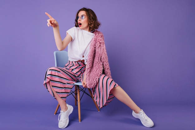 Surprised girl in trendy pants sitting on chair and looking away. indoor portrait of stylish brunette lady in white sneakers expressing amazement during photoshoot on purple wall. Free Photo
