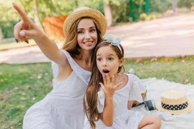 彼女の母親が指で指しているところを見て大きな黒い目を持つ驚いた女の子。ブルネットのかわいい娘と楽しんでいる長い巻き毛の魅力的な若い女性はリボンを着ています。 無料写真