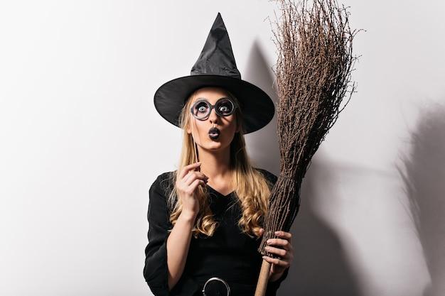 Удивленная девушка с черными губами позирует на карнавале хэллоуина. потрясающая длинноволосая дама в костюме ведьмы, стоящая на белой стене. Бесплатные Фотографии