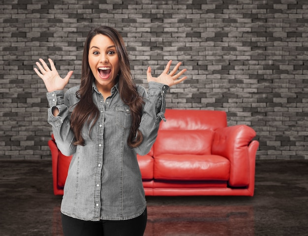Surprised girl with a red sofa background Free Photo