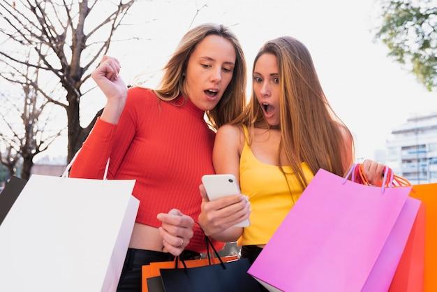 Surprised girls looking at phone Free Photo