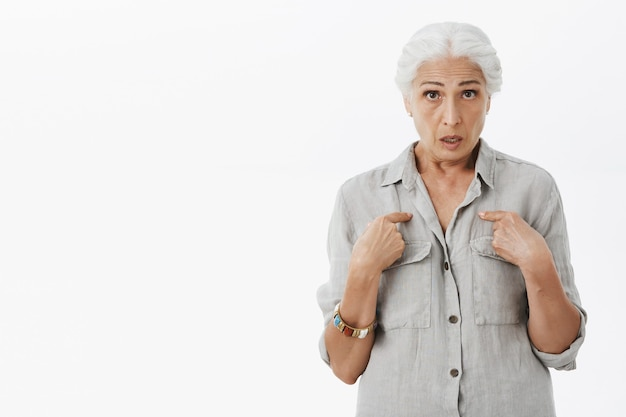 Surprised grandmother asking question and pointing herself Free Photo