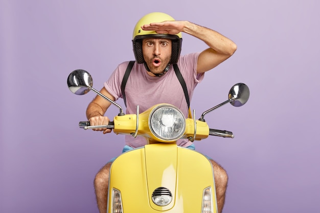 Surprised guy drives fast motorbike, focused into distance, keeps hands on forehead, wears yellow helmet and t shirt, delivers order to customer, isolated on purple wall. shocked motorcyclist Free Photo