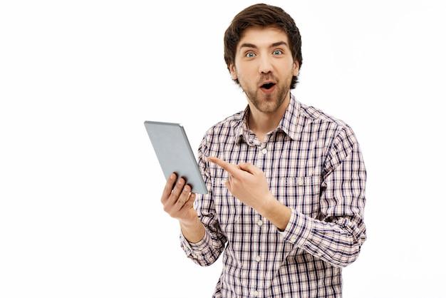 Удивленный парень, указывающий на экран планшета Бесплатные Фотографии
