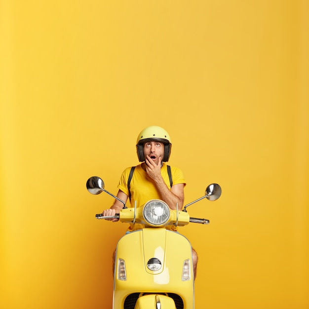 Surprised guy with helmet driving yellow scooter Free Photo
