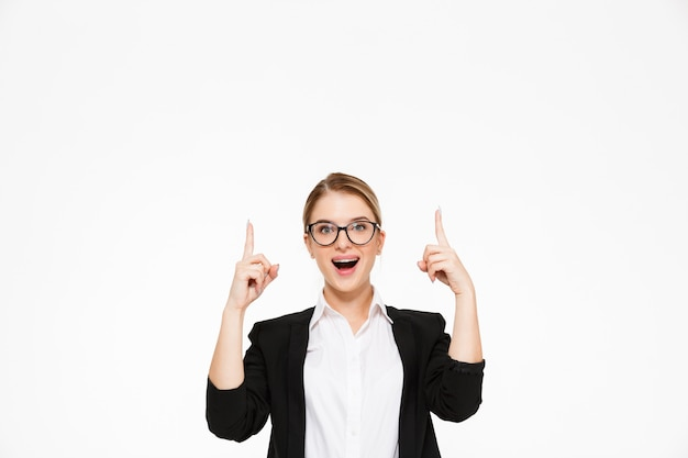 Surprised happy blonde business woman in eyeglasses pointing up Free Photo