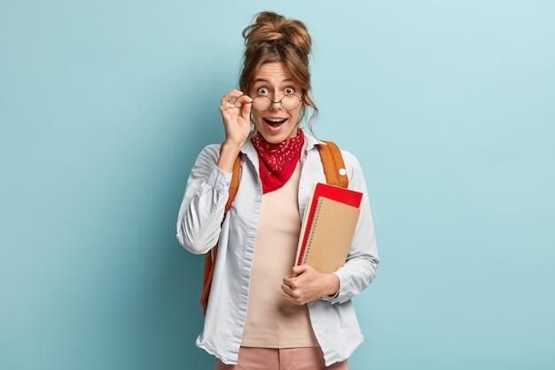 Studentessa felice sorpresa guarda attraverso gli occhiali, tiene la mano sul telaio, trasporta il taccuino a spirale e il libro rosso Foto Gratuite
