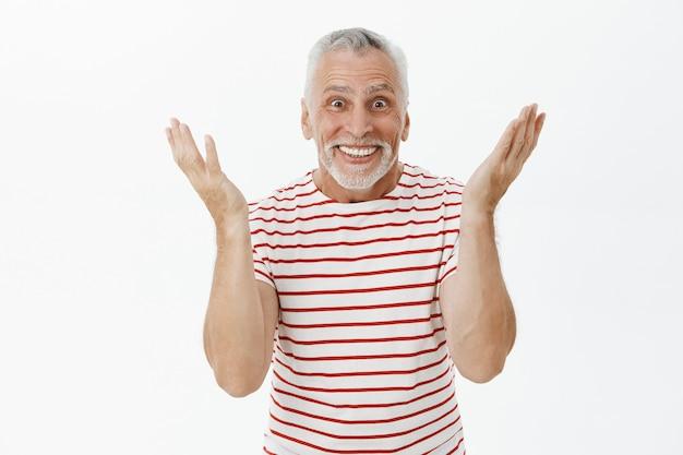 Surprised happy senior man react to wonderful news, smiling cheerful Free Photo