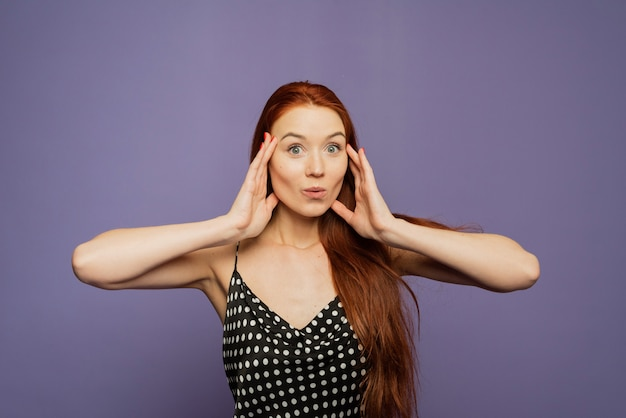 Surprised happy young female stands on purple wall, glad to see big discounts on clothes, expresses shock, keeps hands near head, jaw dropped, going to spend much money today Premium Photo