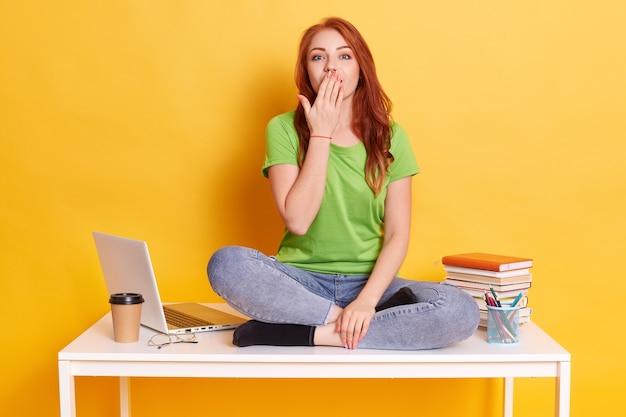 Sorpresa giovane ragazza felice, non posso credere in un trionfo o successo inaspettato, copre la bocca con il palmo, indossa una maglietta verde e jeans, posa contro il muro giallo dello studio Foto Gratuite