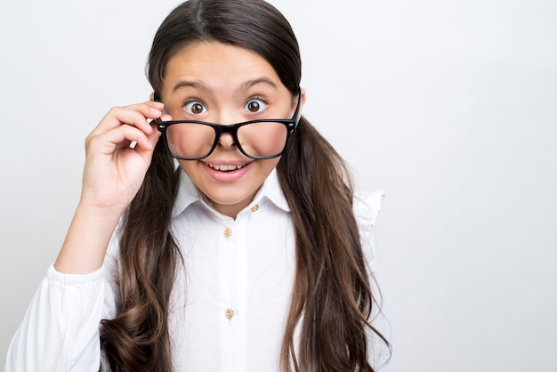 Surprised hispanic schoolgirl straightening glasses. Free Photo