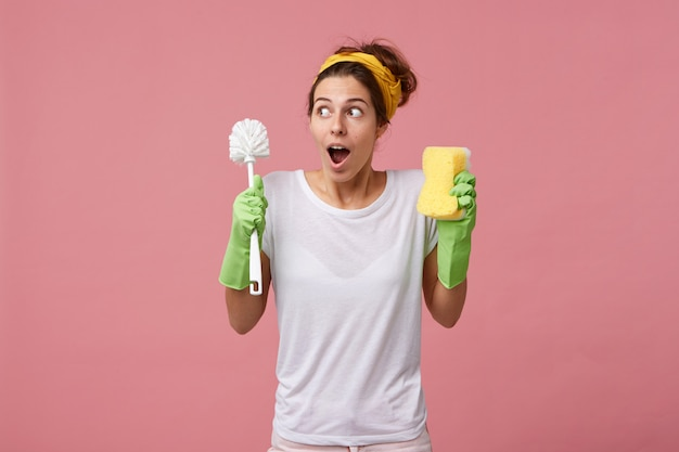 カジュアルな白いtシャツと掃除用の保護手袋を着用した驚いた主婦が部屋のブラシを片付けに行くとき 無料写真