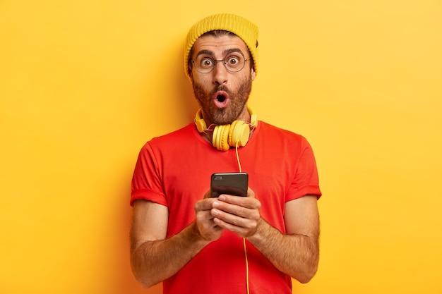 Il maschio sorpreso e impressionato apre la bocca, dimentica il numero di telefono importante, ha le cuffie al collo Foto Gratuite