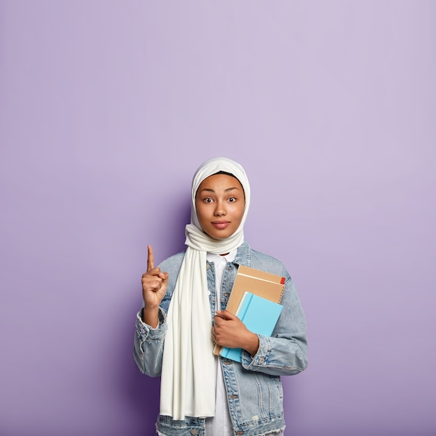 Surprised intriguing woman in headwear points upwards and looks with interest, shows blank space above for your advertisement or information, carries diary and spiral notebook. muslim religion Free Photo