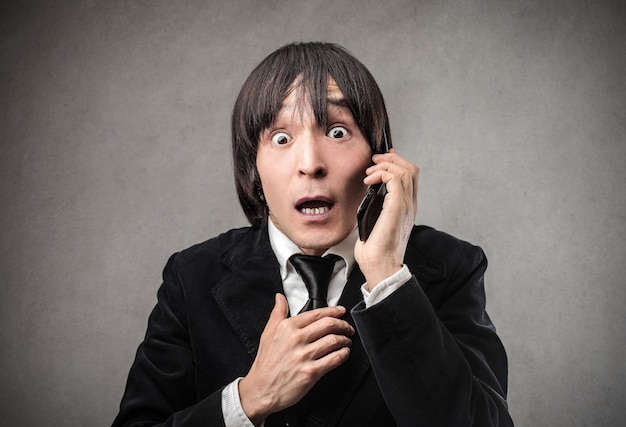 Surprised japanese man talking on the phone Premium Photo