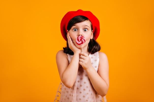 Удивленный ребенок ест леденец на палочке. шокированная девочка десятилетнего возраста с конфетой, изолированной на желтой стене. Бесплатные Фотографии
