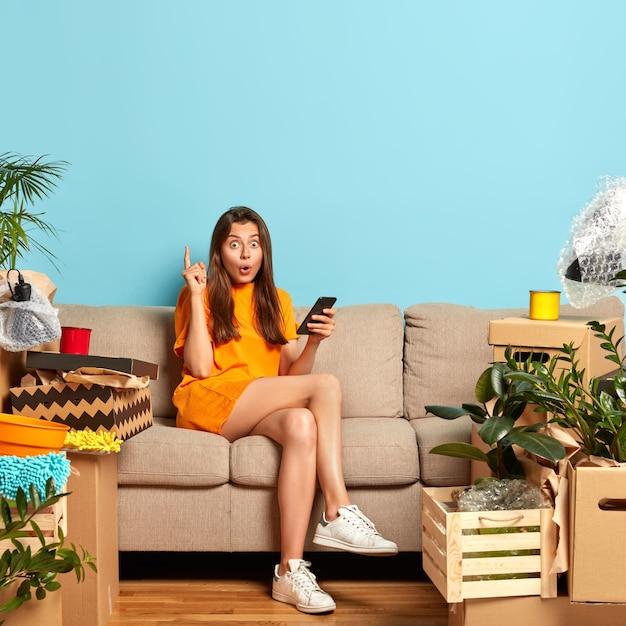 驚いた女性は人差し指を上げ、部屋を設計するための優れたアイデアを得る 無料写真
