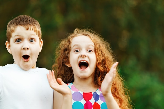 Surprised little girl and boy on spring outdoors. Premium Photo